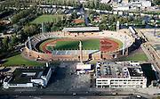 Nederland, Amsterdam, Stadionplein, 25-09-2002; het gerenoveerde Olympisch stadion met daarachter het water van de Schinkel en woonschepen aan het IJsbaanpad; in de voorgrond de Citroengarage, rechtsonder de (omstreden) verplaatste portierswoning; renovatie, monument, cultureel erfgoed, voetbal, atletiek, Olympisch stadion, automobiel verkoop, stadsgezicht;<br /> luchtfoto (toeslag), aerial photo (additional fee)<br /> foto /photo Siebe Swart