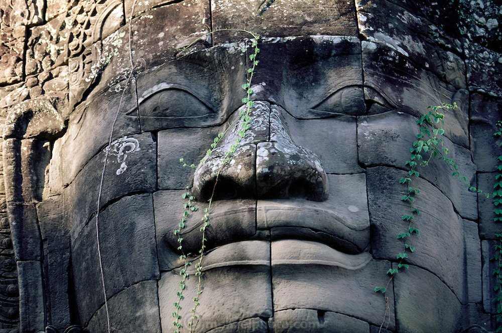 A giant stone face in the Bayon Temple in Angkor, Cambodia. A temple-mountain complex containing 200 gigantic faces. The Banyon is a massive temple complex built by Jayavarman VII between 1181 and 1220. It features 3,936 feet of superb bas-relief carving and mysterious Buddha faces carved on the towers of the third level. The temples at Angkor are spread out over some 40 miles around the village of Siem Reap, about 192 miles from the Cambodian capital, Phnom Penh. They were built between the eighth and 13th centuries and range from single towers made of bricks to vast stone temple complexes. .