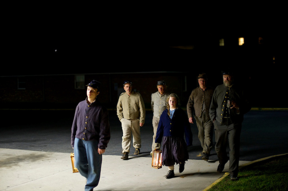 Union and Confederate soldiers are illuminated by the light of a gas station as they stroll past following the first day of battle during the Chancellorsville 150th reenactment on May 4, 2013 in Chancellorsville, VA.