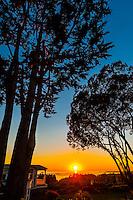 A house at Hope Ranch with the sun setting on the Pacific Ocean behind, Santa Barbara, California USA.