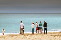 Holidaymakers standing on Fistral beach in Newquay, Cornwall
