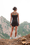 athletic woman standing with her back to the camera looking out over the mountains