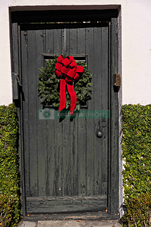December 21, 2017 - Charleston, South Carolina, United States of America - A black wooden door on a historic home decorated with a Christmas wreath on King Street in Charleston, SC. (Credit Image: © Richard Ellis via ZUMA Wire)