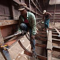 Workers in a boatyard on the Buriganga river in Dhaka, Bangladesh, inside the hull of a ship