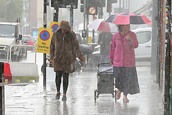 © Licensed to London News Pictures. 18/06/2020. London, UK. A woman shelters from heavy rain underneath an umbrella in north London.  Photo credit: Dinendra Haria/LNP