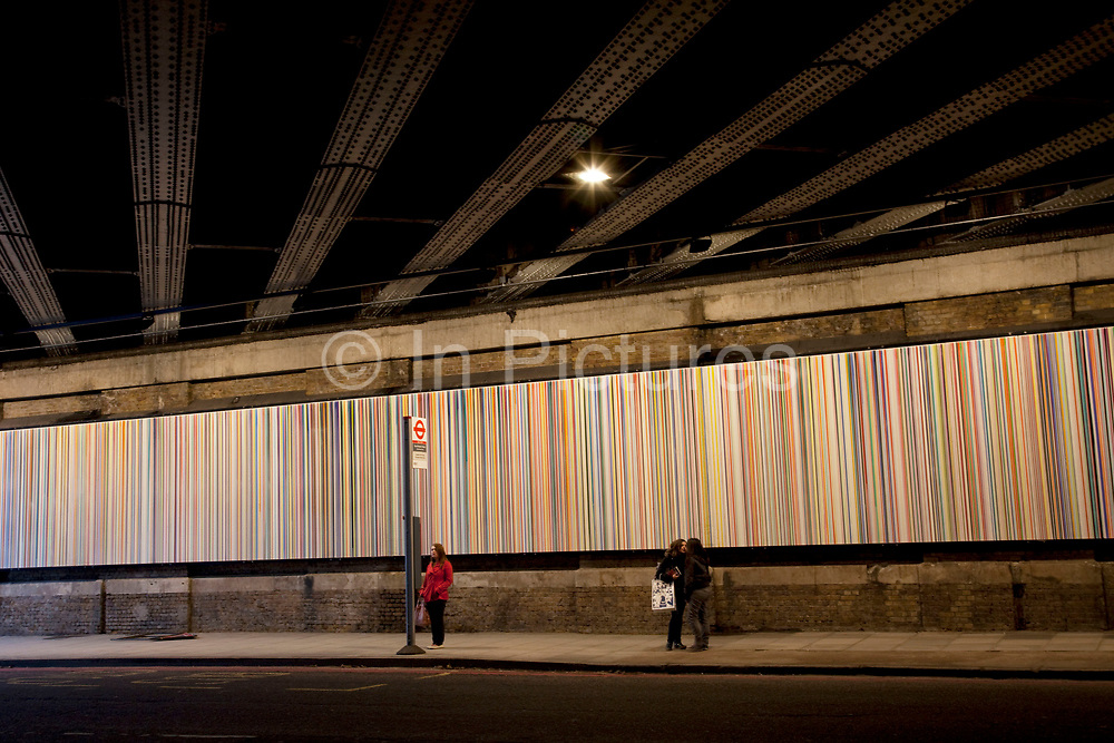 Woman waiting at a bus stop underneath a railway bridge in Southwark, London. An artwork is also installed under the bridge consisting of a striped panel many metres long.
