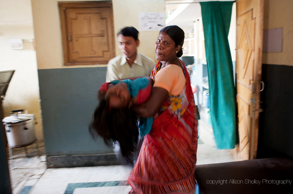 Traditional birth attendant Malti Devi, right, helps rush unconscious patient Muni Devi to a recovery bed after an emergency Caesarean delivery of her first child at Prajapati Nursing Home in the town of Bodhgaya in the state of Bihar, India.