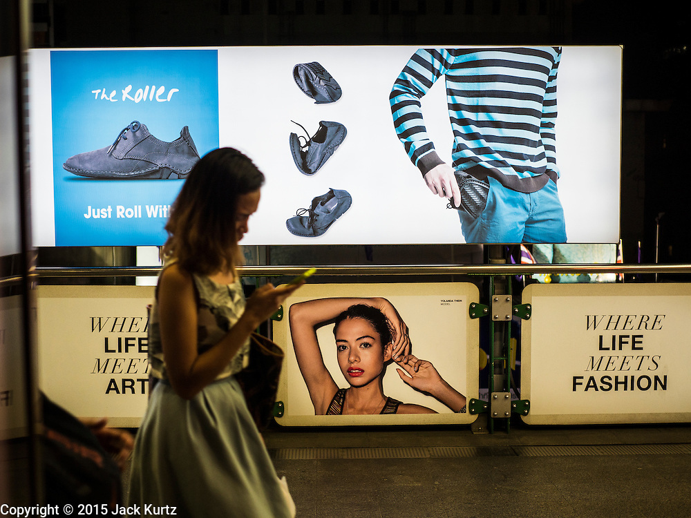 20 MAY 2015 - BANGKOK, THAILAND:   A woman passes an electronic billboard in a BTS station in central Bangkok. Most of the electricity consumed in Bangkok is generated in Laos and Myanmar. In 2013, the Bangkok Metropolitan Region consumed about 40 per cent of the Thailand's electricity, even though the BMR is only 1.5 per cent of the country's land area and about 22 per cent of its population.    PHOTO BY JACK KURTZ