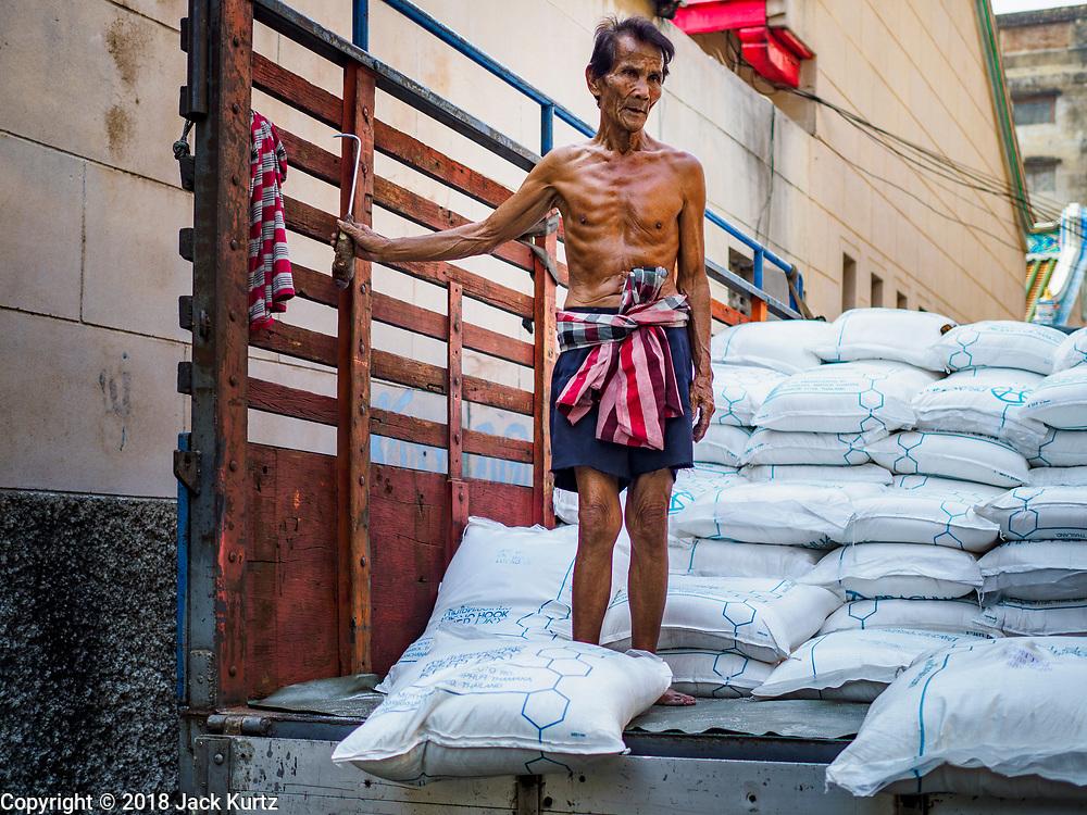 12 FEBRUARY 2018 - BANGKOK, THAILAND: Men unload sugar from a truck at a warehouse in the Chinatown neighborhood of Bangkok.     PHOTO BY JACK KURTZ