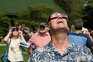 Middletown, New York - A man uses eclipse glasses to watch a partial solar eclipse on Alumni Green at SUNY Orange on Aug. 21, 2017.