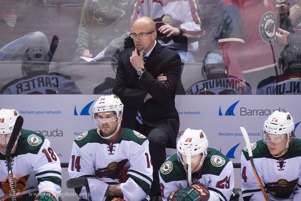December 12, 2015; San Jose, CA, USA; Minnesota Wild head coach Mike Yeo watches from behind the bench during the third period against the San Jose Sharks at SAP Center at San Jose. The Wild defeated the Sharks 2-0.