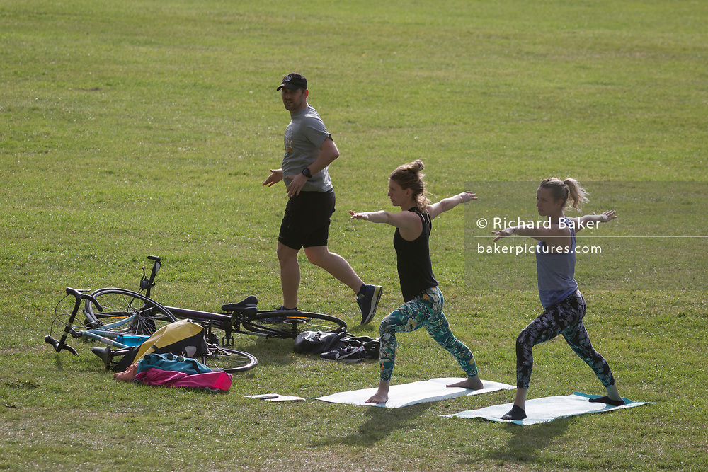 During the UK's government's Coronavirus continuing lockdown restrictions, when a total of 36,393 UK citizens are now reported to have lost their lives, a male runner passes two women practicing yoga in Ruskin Park, a public green space in the south London borough of Lambeth, on 22 May 2020, in London, England.