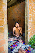"""29 OCTOBER 2012 - MAYO, PATTANI, THAILAND:  A patient at the Bukit Kong home in Mayo, Pattani. He said one of his names is Sukria, but then added, """"I have so many names I don't remember who I am anymore."""" He is kept shackled in his room at the home. The home opened 27 years ago as a ponoh school, or traditional Islamic school, in the Mayo district of Pattani. Shortly after it opened, people asked the headmaster to look after individuals with mental illness. The headmaster took them in and soon the school was a home for the mentally ill. Thailand has limited mental health facilities and most are in Bangkok, more than 1,100 kilometers (650 miles) away. The founder died suddenly in 2006 and now his widow, Nuriah Jeteh, struggles to keep the home open. Facilities are crude by western standards but the people who live here have nowhere else to go. Some were brought here by family, others dropped off by the military or police. The home relies on donations and gets no official government support, although soldiers occasionally drop off food. Now there are only six patients, three of whom are kept chained in their rooms.  Jeteh says she relies on traditional Muslim prayers, holy water and herbal medicines to treat the residents. Western style drugs are not available and they don't have a medic on staff.    PHOTO BY JACK KURTZ"""