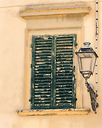 A window in an old yellow-tinged building in Montespertoli, Italy is covered with flaking green-painted shutters.