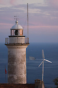 Turkey, Antalya Province, Olympos National Park, Cape Gelidonya. The lightghouse at dusk The wind turbine producing green electricity for the lighthouse in the background
