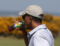 Former US president Barack Obama drinks from a bottle of Lipton lemon ice tea after stopping at a snack bar while playing a round of golf at the Old Course in St Andrews, Fife.