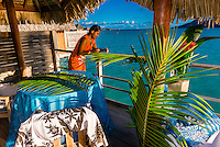 A Polynesian woman setting up a private romantic dinner on the deck of an overwater bungalow, Four Seasons Resort Bora Bora, French Polynesia.
