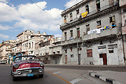 Old Amercian car in excellent condition driving through the run down dilapidated streets of old Havana