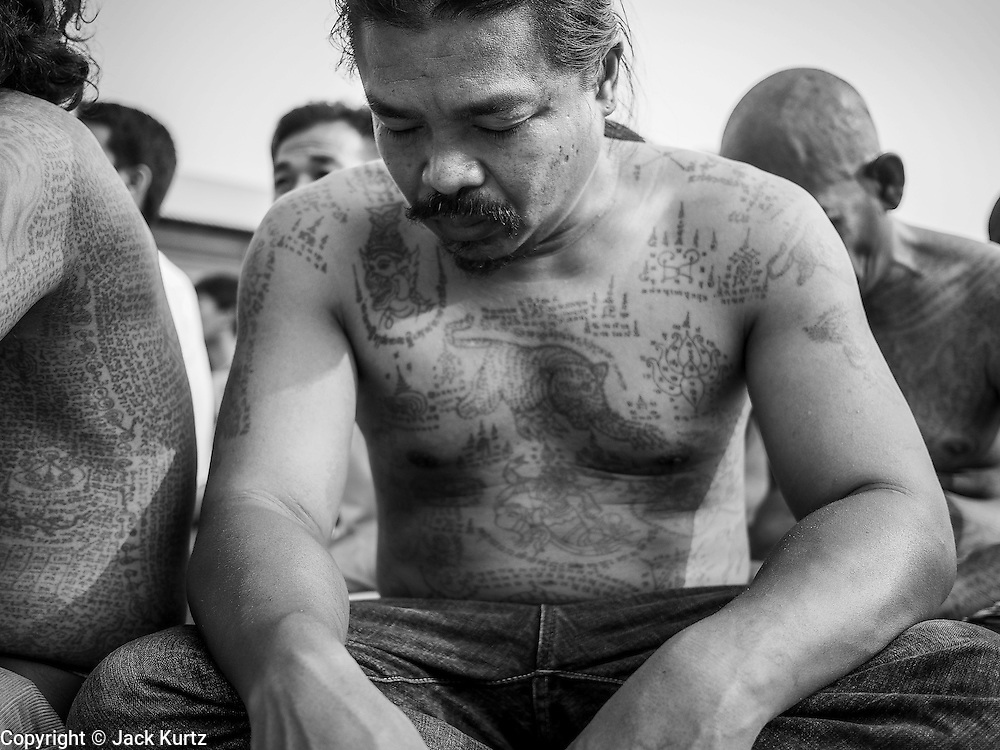 """15 MARCH 2014 - NAKHON CHAI SI, NAKHON PATHOM, THAILAND: A man covered in tattoos prays at the Wat Bang Phra tattoo festival. Wat Bang Phra is the best known """"Sak Yant"""" tattoo temple in Thailand. It's located in Nakhon Pathom province, about 40 miles from Bangkok. The tattoos are given with hollow stainless steel needles and are thought to possess magical powers of protection. The tattoos, which are given by Buddhist monks, are popular with soldiers, policeman and gangsters, people who generally live in harm's way. The tattoo must be activated to remain powerful and the annual Wai Khru Ceremony (tattoo festival) at the temple draws thousands of devotees who come to the temple to activate or renew the tattoos. People go into trance like states and then assume the personality of their tattoo, so people with tiger tattoos assume the personality of a tiger, people with monkey tattoos take on the personality of a monkey and so on. In recent years the tattoo festival has become popular with tourists who make the trip to Nakorn Pathom province to see a side of """"exotic"""" Thailand.   PHOTO BY JACK KURTZ"""