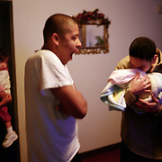11/15/02<br />Angel kisses his new nephew as his younger brother, Timothy, and sister Debbie look on early in the morning of Angel's first day back home.