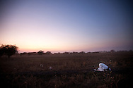 A man prays at dusk near South Sudan's richest oli deposit.