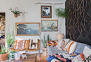 Liz Kamarul's living room is artistically decorated in a bohemian fashion with wares found at second hand stores. From the vine that climbs wires fixed from floor to ceiling, to the wall covered in a pattern of black triangles, the space showcases creative ideas and home decor that is affordable and accessable to many. The wall was originally supposed to have a linear pattern of black triangles, but when she laid it out and her dog ran by scrambling the pieces, she found a new arrangement. And the room is all centered around the notrious couch that caused her instragram following to surge!  <br /> Image by Shauna Intelisano