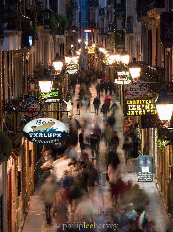 A busy street with bars and restaurants at night in the city of San Sebastian, Spain
