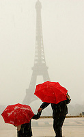 The Eiffel Tower with bright umbrelled visitors during a sudden hail storm, February 13, 2005