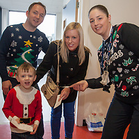 Donal Higgins with his wife Michelle and son Dylan from Newmarket on Fergus, receiving their boarding pass for their Santa Flight from Swissport's Dawn Ahearn