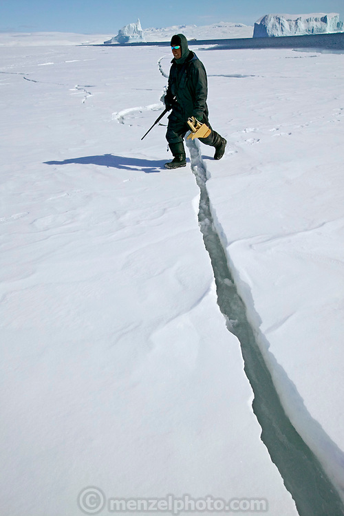 (MODEL RELEASED IMAGE). Taking special care about cracks in the ice, Emil Madsen selects the best spot for some on-shore seal hunting. In the spring this can be dangerous because the ice is breaking up and sometimes huge pieces break off and move out to sea. He is carrying a rifle and home-made wooden gun support. Giant iceberg in background  in the open water beyond the sea ice edge.(Supporting image from the project Hungry Planet: What the World Eats.)