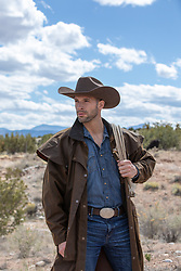 rugged cowboy in a duster on a ranch