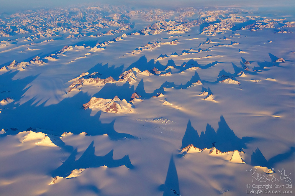 The midnight sun causes the peaks of eastern Greenland to cast long shadows over the frozen landscape near Milait. The northern face of these mountains is lit by the sun, something that happens only in the middle of the night in the Greenland summer. Because of the extreme northern latitude, sunlight spills over the top of the Earth to illuminate these peaks at night.