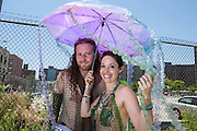 Brooklyn, NY - 18 June 2016. A couple covered in fishnet costumes under a jellyfish-like umbrella prior to taking their places in the parade.
