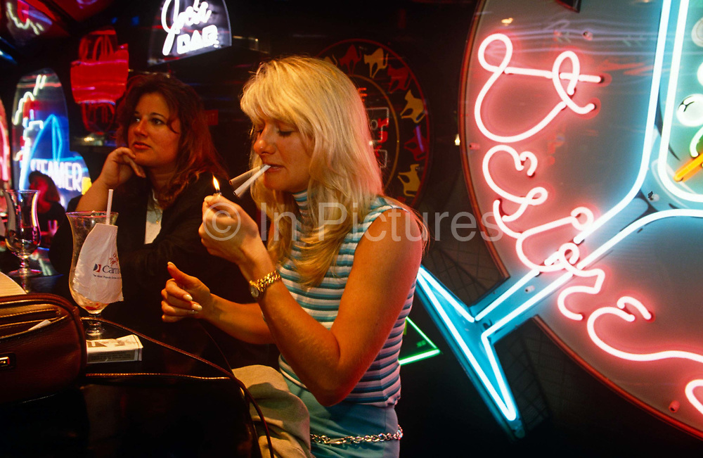 En-route to Cancun in Mexico, two lady passengers of Carnival Cruise's Fun Ship Ecstasy are seated at The Neon Bar one evening. Lighting a cigarette that has been duplicated by the action of camera flash and ambient light, one of the girls has a packet of Marlboros on the bar plus an empty cocktail glass that has a Carnival Cruises napkin which has stuck to the glass. The Neon Bar features an enormous circular piano which doubles as a bar for those who like to sing along and neon artwork is lit behind the females, one the shape of another cocktail glass. Carnival's ships are known for their Las Vegas decor and entertainment. The cruise line calls its ships The Fun Ships and the MS Ecstasy is a Fantasy class cruise ship featuring two pools, whirlpools, a variety of dining options, nightclubs, a casino, and duty-free shopping.