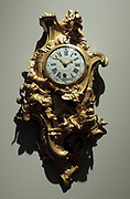 Cartel clock by Jacques Caffieri (1678-1755) Paris, c 1741.  Movement Julien le Roy (1686-1759) gilt, bronze.  The renowned artist Caffieri signed the case of this cartel (or wall) clock, just like a painter signs a painting.  The asymmetrical Rococo case shows the figure of Diana, goddess of the moon, looking down tenderly upon the sleeping Endymion.  They are set in an imaginary framework of rocoilles, plants, architectural elements and abstract motifs.