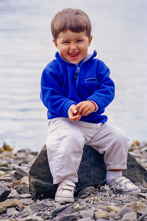 Happy Toddler Playing with Pebbles on Beach ****Model Release available