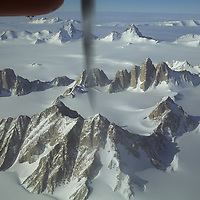 ANTARCTICA. Twin Otter ski plane flies over Organ Pipe Peaks in Gothic Mountains, a subrange of Queen Maud Mountains, in the vast Trans-Antarctic Mountains. Sanctuary Glacier behind Organ Pipes.  1900m Mount Harkness foreground.  Bkg. (L to R): Mount Danforth, 2481m Mount Andrews, 2520m Mount Gerdel, Peak 2340. Far bkg: 2385m Mount Gould & 2524m Mount Andes (R), behind Albanus Glacier.  Horizon is Leverett Glacier. Lower Left is Scott Glacier.
