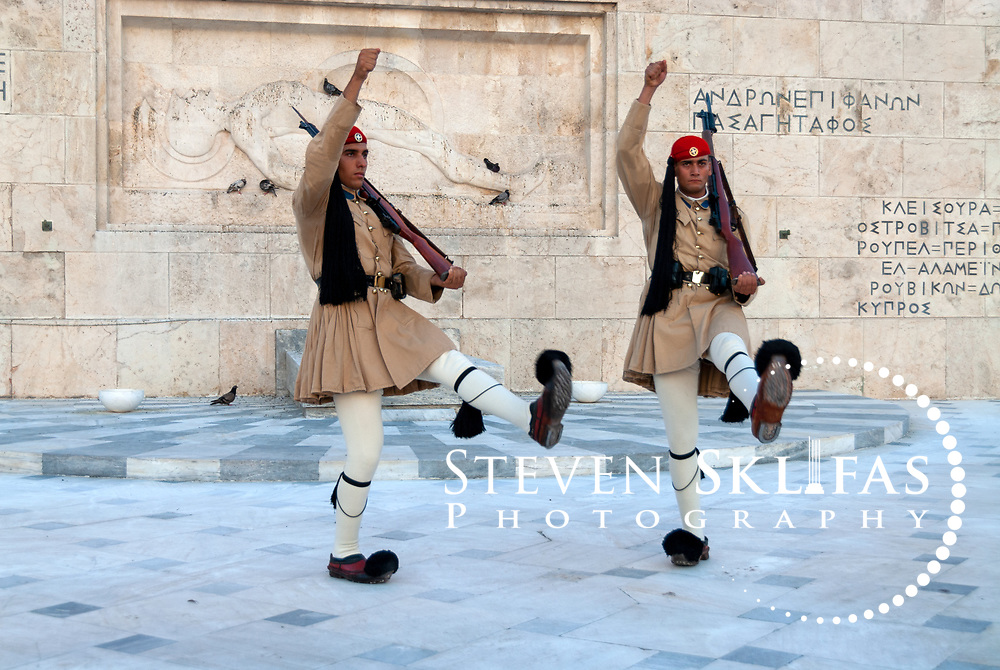 Syntagma square. Athens. Greece. View of Greek Evzones performing the very slow and highly stylized ceremonial changing of the guard at the monument to the Unknown Soldier in Athens. The monument to the Unknown Soldier, erected in 1929-1932, depicts a relief of a dying Greek solider and is watched around the clock by pairs of Evzones, elite members of the Presidential ceremonial guard unit, standing motionless outside their sentry boxes wearing traditional dress. These guards are wearing the summer service uniform tunic that is light khaki in colour.