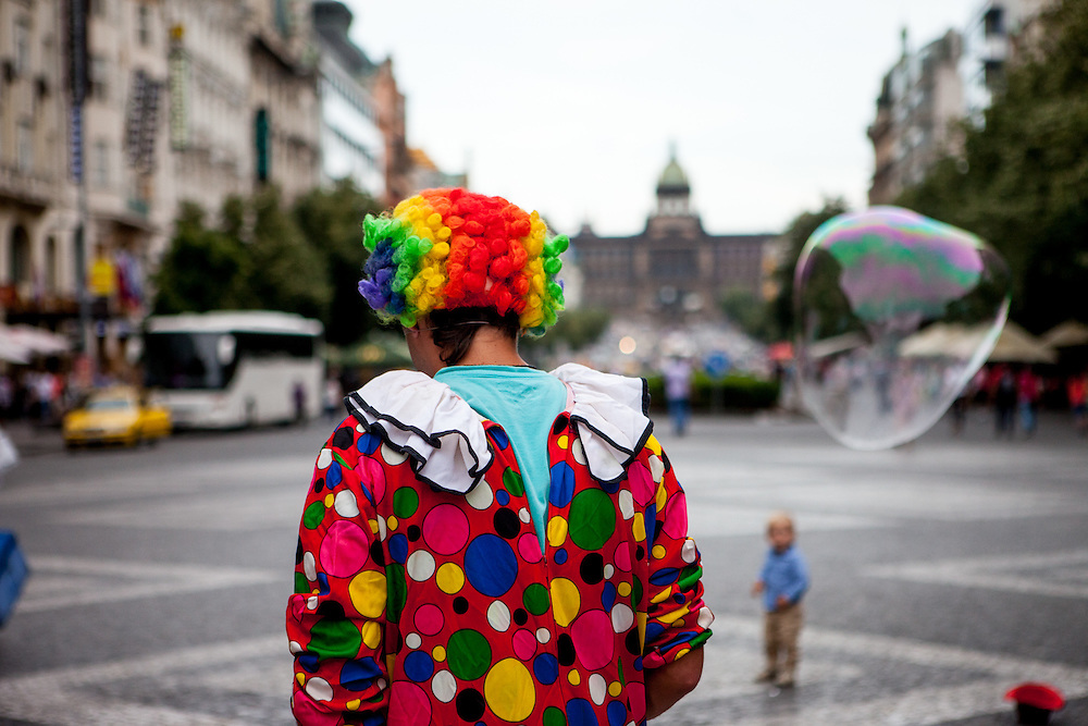 """A clown is doing a """"bubble"""" performance at Wenceslas Square in Prague."""