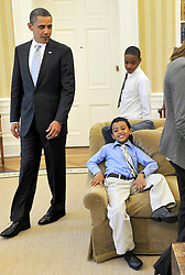 """""""U.S. President Barack Obama President looks at Francisco, a first grade student from Bronx, New York, one of the students from the movie """"""""Waiting for Superman"""""""" who is making himself comfortable on a sofa in the Oval Office of the White House in Washington, D.C. on Monday, October 11, 2010.  Looking on is Anthony, a fifth grader from Washington, D.C. Photo by Ron Sachs/ABACAPRESS.COM""""  