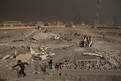Licensed to London News Pictures. 08/11/2016. Qayyarah, Iraq. Smoke from burning oil facilties fills sky as men stack concrete blocks and young Iraqi boys play amongst the destroyed football stadium in Qayyarah, Iraq. The stadium was targeted by an Iraqi or coalition airstrike as it was the location for an ISIS headquarters. Oil wells in and around the town of Qayyarah, Iraq, we set alight in July 2016 by Islamic State extremists as the Iraqi military began an offensive to liberated the town.<br /> <br /> For two months the residents of the town have lived under an almost constant smoke cloud, the only respite coming when the wind changes. Those in the town, despite having been freed from ISIS occupation, now live with little power, a water supply tainted with oil that only comes on periodically and an oppressive cloud of smoke that coats everything with thick soot. Many complain of respiratory problems, but the long term health implications for the men, women and children living in the town have yet to be seen. Photo credit: Matt Cetti-Roberts/LNP