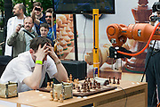 Moscow, Russia, 19/05/2012..Russian grandmaster and former World Blitz Chess Champion Alexander Grischuk plays a demo match against the German-built KUKA Monster chess robot. The match was a warm up before the main contest between KUKA Monster and Russia?s CHESSka robot for the title of Absolute World Robot Chess Champion. KUKA Monster easily beat the human Russian grandmaster, but was in turn comprehensively defeated by the Russian robot.