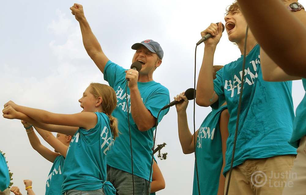 A youth group performs a worship song before before taking an outdoor baptizing event at Willow Creek Community Church in South Barrington, IL on June 26, 2005. The church holds regular mass baptisms at which hundreds of people are baptized in the church's small lake.