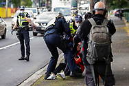 A woman standing on the street in support of the residents inside of 120 Racecourse road is violently slammed to the ground and arrested as police swarm on a small number of people amid the third full day of the total lockdown of 9 housing commission high rise towers in North Melbourne and Flemington during COVID 19.After recording 191 COVID-19 cases overnight forcing Premier Daniel Andrews to announce today that all of metropolitan Melbourne along with one regional centre, Mitchell Shire will once more go back to stage three lockdowns from midnight Wednesday June 8. This comes as the residents of the housing commission towers in North Melbourne and Flemington finish their third day under extreme lockdown, despite only 27 cases being found in the towers. Members of the public gathered outside of the towers this afternoon in support of those trapped inside while riot police arrested two women for standing too close to the fence. While the women were later released, tensions are boiling over both in the towers and out. With 772 active cases in Victoria, NSW closed their border to Victoria effective at midnight tonight.