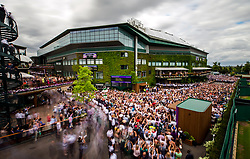 Crowds gather outside centre court as Roger Federer parades the trophy on a centre court balcony after beating Marin Cilic in the Gentlemen's Singles Final on day thirteen of the Wimbledon Championships at The All England Lawn Tennis and Croquet Club, Wimbledon.