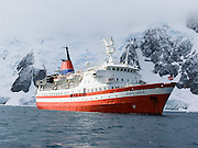 The ship M/S Explorer cruises by tidewater glaciers in the Southern Ocean at Graham Land, in Antarctica.