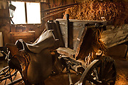 Old style agricultural tools in a wooden shed. horse drawn Wagon with saddle