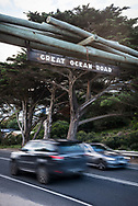 Two cars pass each other under a welcome sign on the Great Ocean Road in Victoria, Australia.