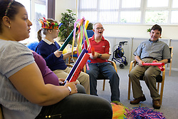 Day Service Assistant working with service users with learning disability at a music session,