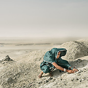 """Some of the pilgrims build tiny mounds out of hard mud. It symbolizes a home, and they do that to wish for a house either for themselves, or for one of their relatives. Pilgrims arriving at Chandragup (meaning """"Moon Well""""), a sacred site to Hindu of 3 mud volcanoes (including mainland Asia's largest one)."""